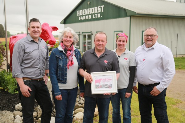 Wensink family and team members at Hoenhorst Farms, Ltd receiving red Lely cow.