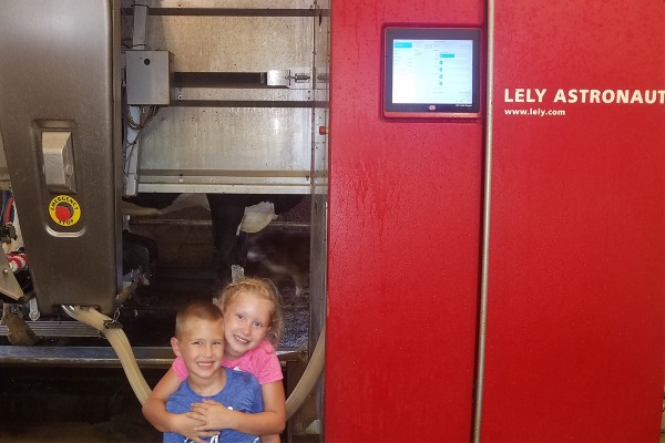 Maggie and Max of Wolff Farms with their family's Lely Astronaut A4 automatic milking system.