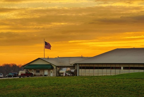 Dairy barn refitted for milking robots pictured at sunset.