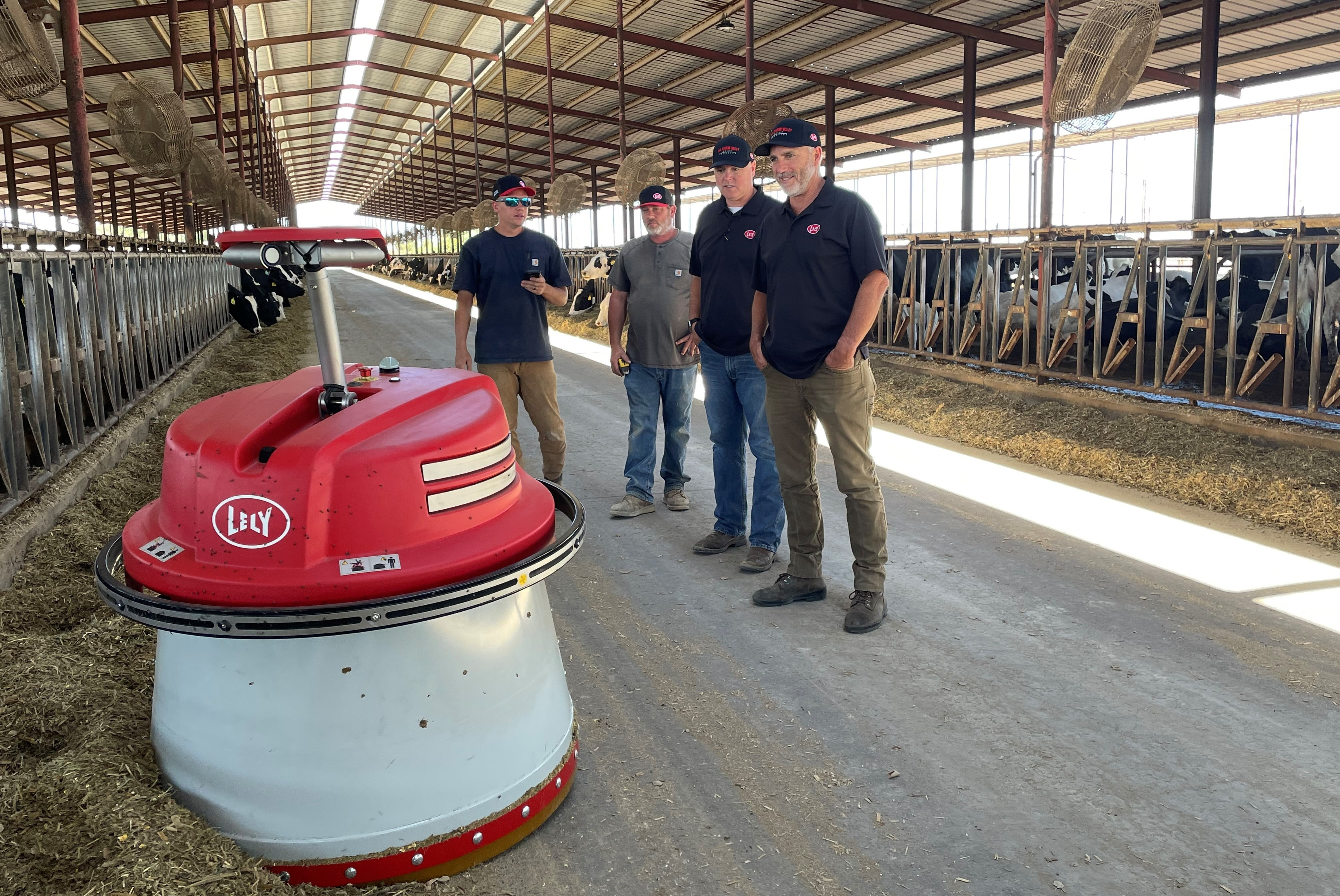 San Joaquin Valley Dairy Robotics team inspecting the Lely Juno automatic feed pusher